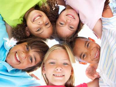 Five Smiling Kids Huddled Looking Down at Camera for ChildLife Nutritional Supplements for Kids Blog Post on Top Four Nutrient for Your Child