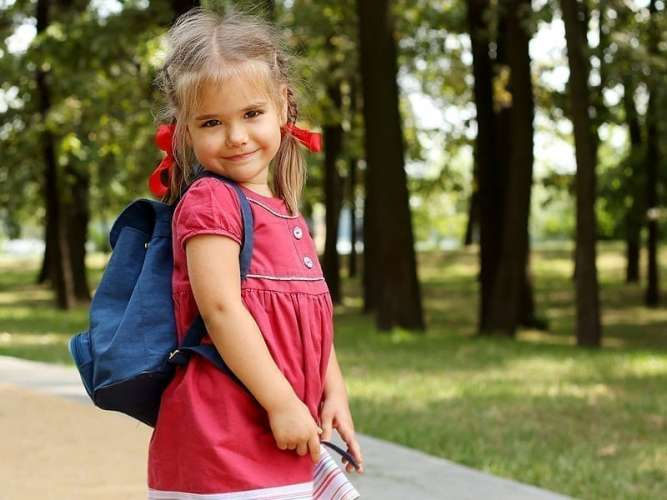 Little Girl in Red Dress and Braids with Blue Backpack for ChildLife Nutritional Supplements for Kids Blog Post on Back to School