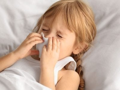 Little Girl in Bed Blowing Her Nose for ChildLife Nutritional Supplements for Kids Blog Post on Cold and Flu Season